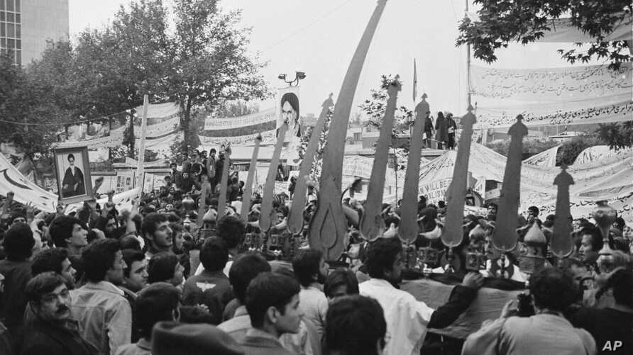 Religious symbols are held up outside the U.S. Embassy gates in Tehran, Iran, where students hold American hostages, on Nov. 28, 1979.