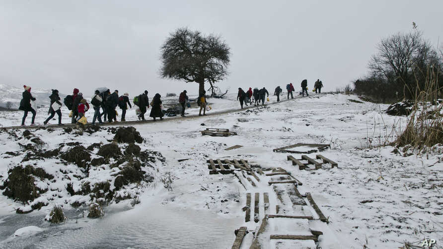 FILE - Migrants cross a frozen stream as they walk through a snowstorm from the Macedonian border into Serbia, near the village of Miratovac, Serbia, Jan. 18, 2016.
