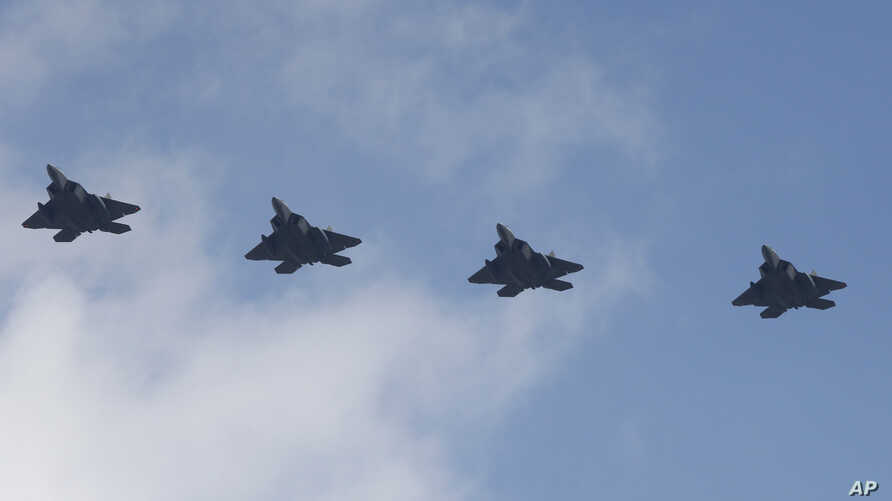 Four U.S. F-22 stealth fighters fly over Osan Air Base in Pyeongtaek, South Korea, Wednesday, Feb. 17, 2016.