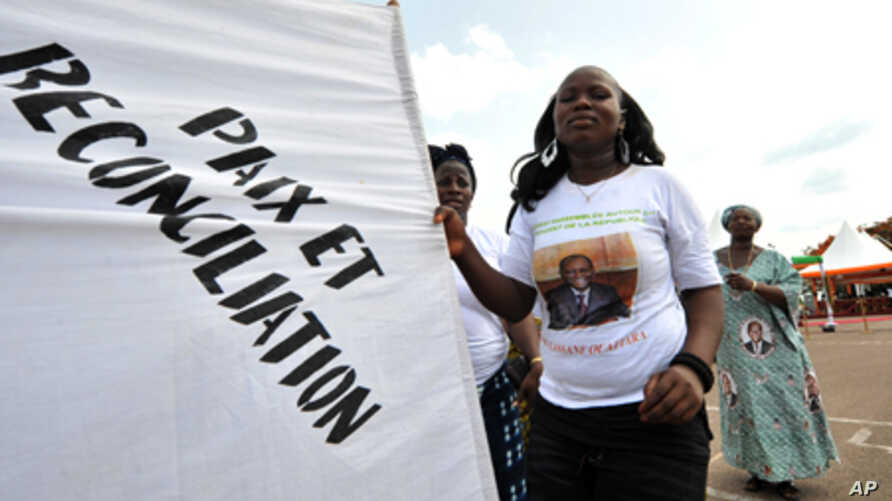 """A supporter of Ivorian President Alassane Ouattara dances as she holds a banner reading in French """"Peace and reconciliation"""" during a meeting on April 22, 2012 in Guiglo."""