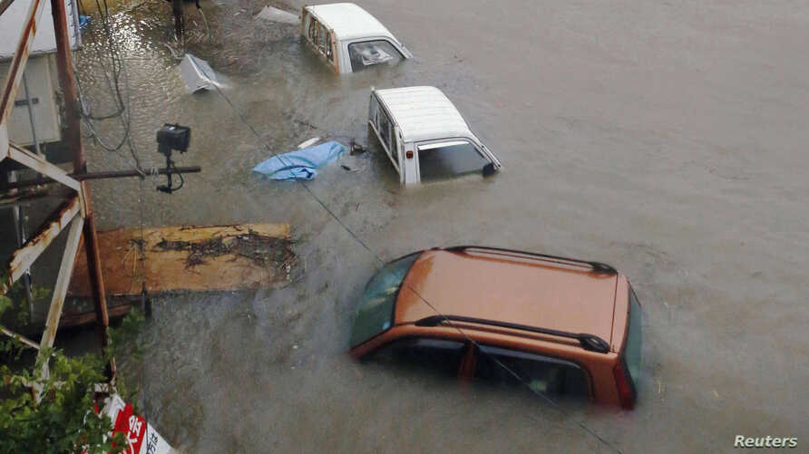 Stranded cars are seen in floodwater caused by Typhoon Halong in Kochi, western Japan, Aug. 10, 2014.