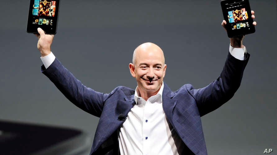 """Amazon CEO Jeff Bezos holds up the new Kindle Fire HD 7"""" and Kindle Fire HD 8.9"""" (L) during Amazon's Kindle Fire event in Santa Monica, California Sep. 6, 2012."""