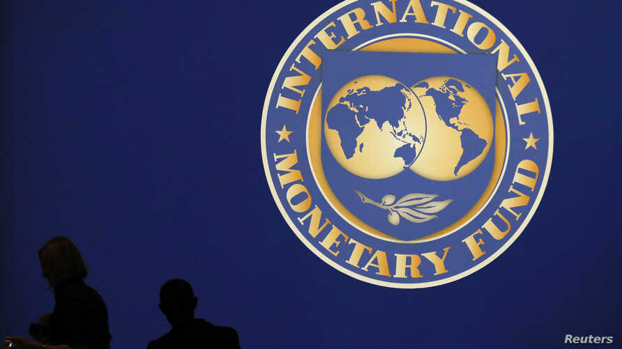 Visitors are silhouetted against the logo of the International Monetary Fund at the main venue for the IMF and World Bank annual meeting in Tokyo, October 10, 2012.