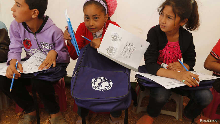 FILE - Syrian refugee children attend an English lesson inside a makeshift school tent during a visit by UNICEF Executive Director Anthony Lake.
