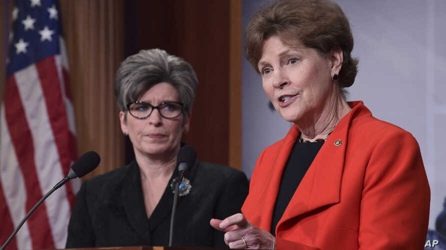 """Sen. Jeanne Shaheen, D-N.H., right, standing with Sen. Joni Ernst, R-Iowa, announces in Washington, Feb. 7, 2018, a bipartisan resolution that would """"establish a special committee in the Senate to investigate the U.S. Olympic Committee and USA Gymnas"""