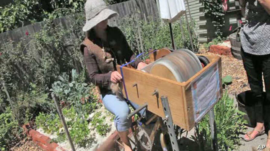 Katherine Jolda pedals to power two large spinning metal drums that brush out wool to be used for locally-made clothing and accessories.