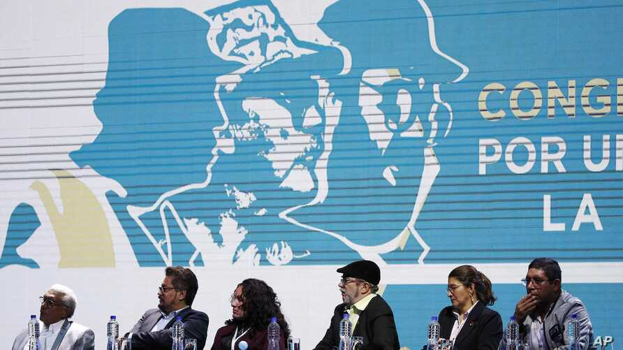 FILE - Leaders of the Revolutionary Armed Forces of Colombia (FARC), sit before former guerrillas as they lead the FARC's National Congress where they launched their political party in Bogota, Colombia, Aug. 27, 2017. The former leftist rebels have c
