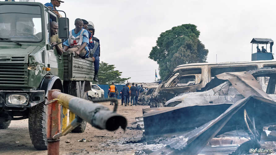 Security personnel sitting on a truck watch burned vehicles at the front gate of the Makala prison after it was attacked by supporters of jailed Christian sect leader Ne Muanda Nsemi in Kinshasa, Democratic Republic of the Congo, May 17, 2017.