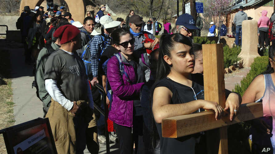 Jasmin Perez, 17, of Espanola, New Mexico, carries a cross on a pilgrimage to a small adobe church in Chimayo, New Mexico, March 30, 2018. She joined thousands of Catholics who traveled by foot to El Santuario de Chimayo in the hills of northern New