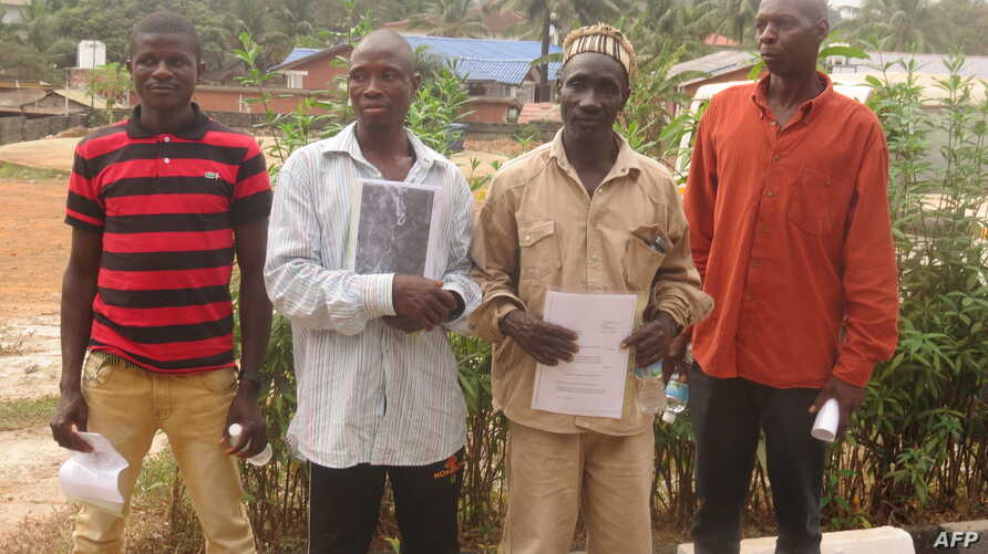 (L-R) Manso Turay, James Conteh, Father Kargbo, Mohamed Barrie pose outside the Radisson hotel in Freetown on Feb. 5, 2018, before a hearing where a British court heard testimony of the alleged complicity of a British mining company in police brutali