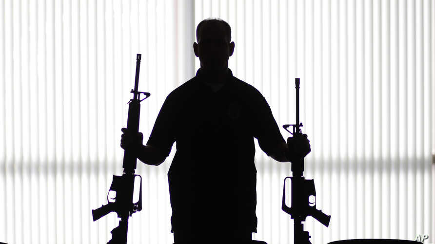 FILE - An agent of the U.S. Bureau of Alcohol, Tobacco, Firearms and Explosives holds guns at an ATF field office in Glendale, Calif., Aug. 29, 2017.