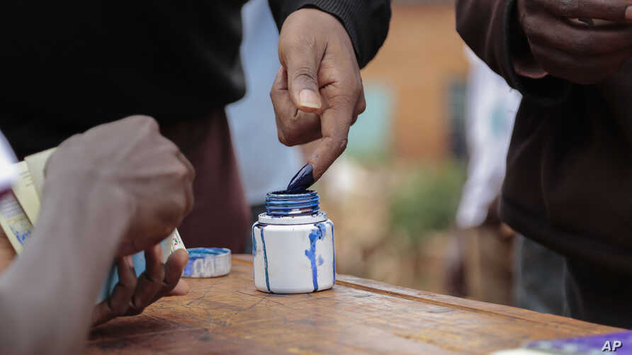 A Burundian official marks a voter's finger with ink after voting in parliamentary elections in Ngozi, Burundi, June 29, 2015.