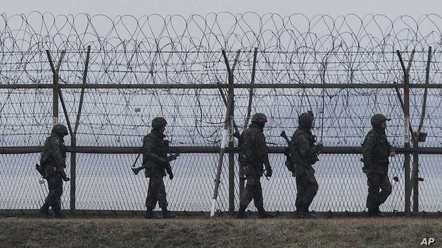 South Korean army soldiers patrol along a barbed-wire fence near the border village of the Panmunjom, in Paju, South Korea, April 8, 2013.