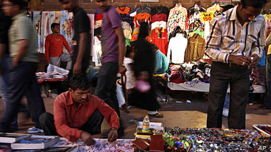 Indians walks past roadside stalls selling clothes and miscellaneous items in New Delhi, India. Indian Finance Minister, Mukherjee, presented India's new budget amid concerns about inflation, the country's falling growth rate, large deficit, FILE Mar