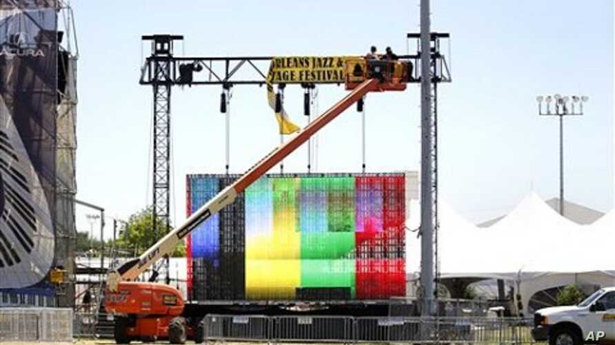Workers hang signs in preparation for the New Orleans Jazz and Heritage Festival in New Orleans, April 28, 2011