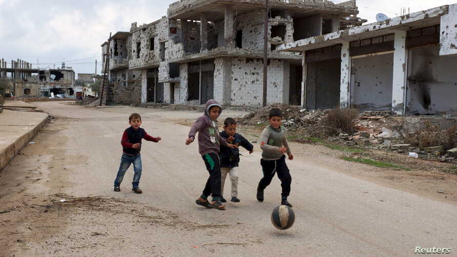 Children play near damaged buildings in the rebel-held southern town of Bosra al-Sham, Deraa, Syria, Feb. 23, 2016. Negotiations continue on a proposed cease-fire.