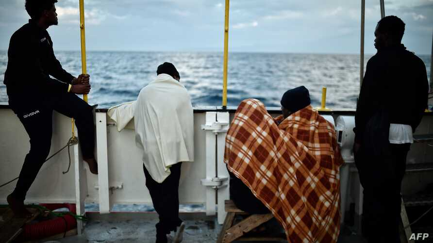 FILE - Migrants look at the coastline as they stand aboard a rescue ship, off the coast of Sicily, May 14, 2018.