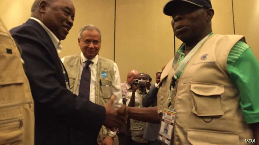 Former Nigerian President Olusegun Obasanj, right, greets former Zambian President Rupiah Banda after a news conference held by Commonwealth Observers team in Kampala, Feb. 20, 2016. Obasanjo heads Commonwealth Observers and Banda heads the Electoral...