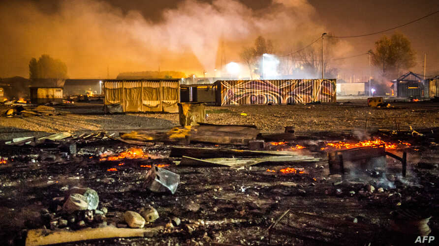 Grande-Synthe migrant camp smolders early April 11, 2017 outside the northern French city of Dunkirk, after a huge fire.