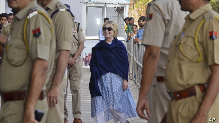 In this Thursday, March 15, 2018 photo, former U.S. Secretary of State Hillary Clinton, center, arrives at the departure terminal of Jodhpur airport in Rajasthan state, India.