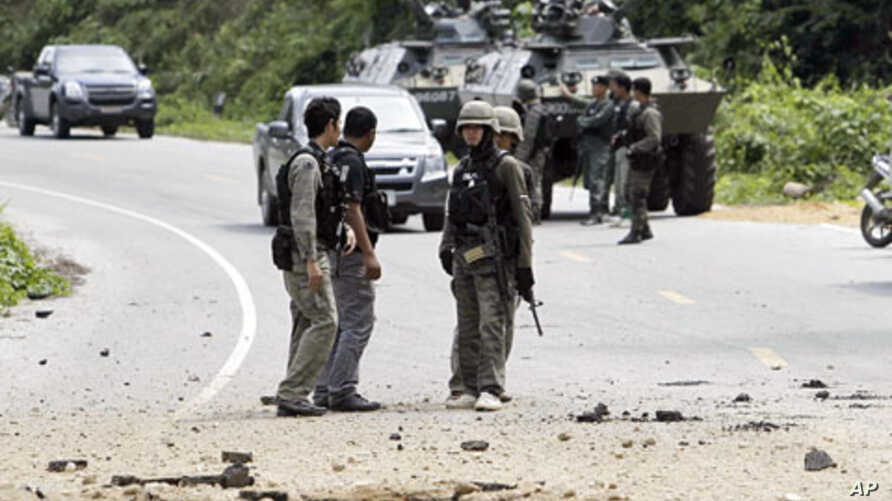 Thai security personnel inspect the site of the bomb attack on a patrol in which two policemen were wounded in the southern Yala province . In a separate attack, suspected Muslim separatists killed four soldiers and wounded five others, 20 Jan 2011.