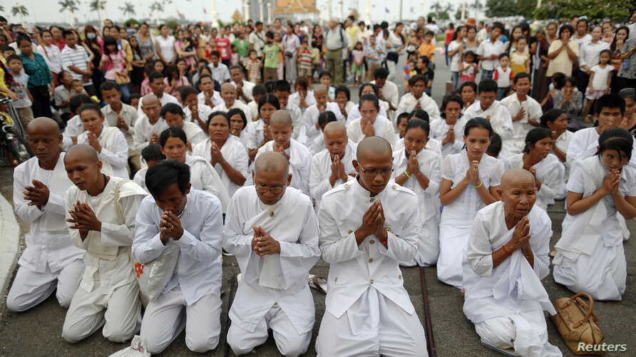 People wearing white pray as they mourn the late Cambodia's former King Norodom Sihanouk in front of the Royal Palace in Phnom Penh, October 15, 2012.