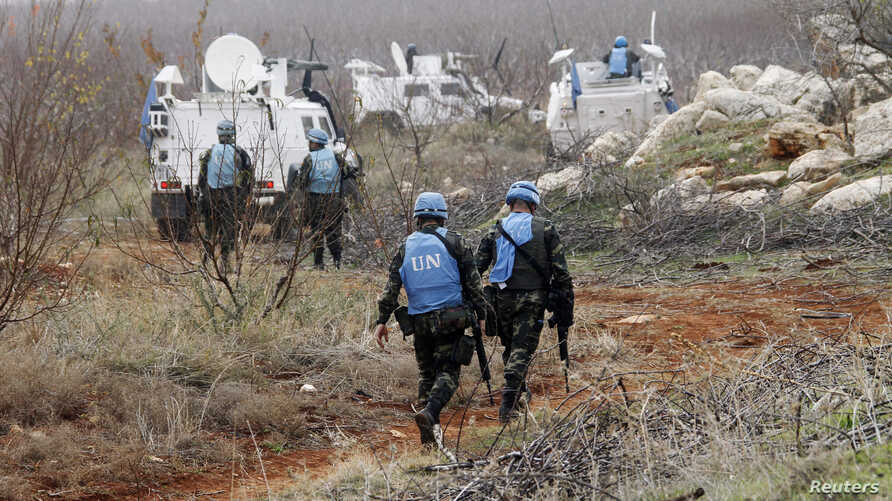United Nations Interim Force in Lebanon (UNIFIL) troops inspect the remains of a shell that was launched from Lebanon to Israel, which according to activists landed 500m from the Lebanese-Israeli border, in the southern Lebanese village of Sarada Dec