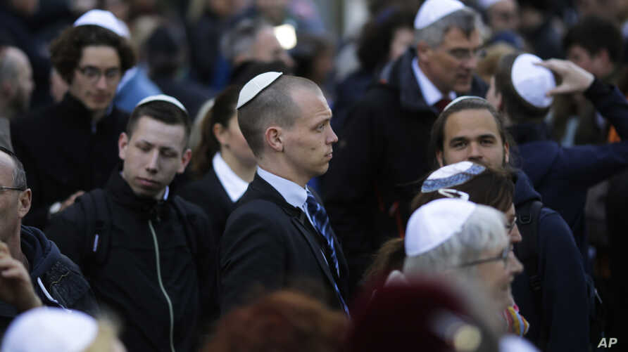 People wear Jewish skullcaps - or kippas, as they attend a demonstration against an anti-Semitic attack, in Berlin, Germany, April 25, 2018.