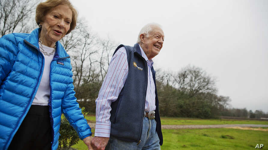 FILE - Former President Jimmy Carter, right, and his wife Rosalynn arrive for a ribbon cutting ceremony for a solar panel project on farmland he owns in their hometown of Plains, Ga., Wednesday, Feb. 8, 2017.