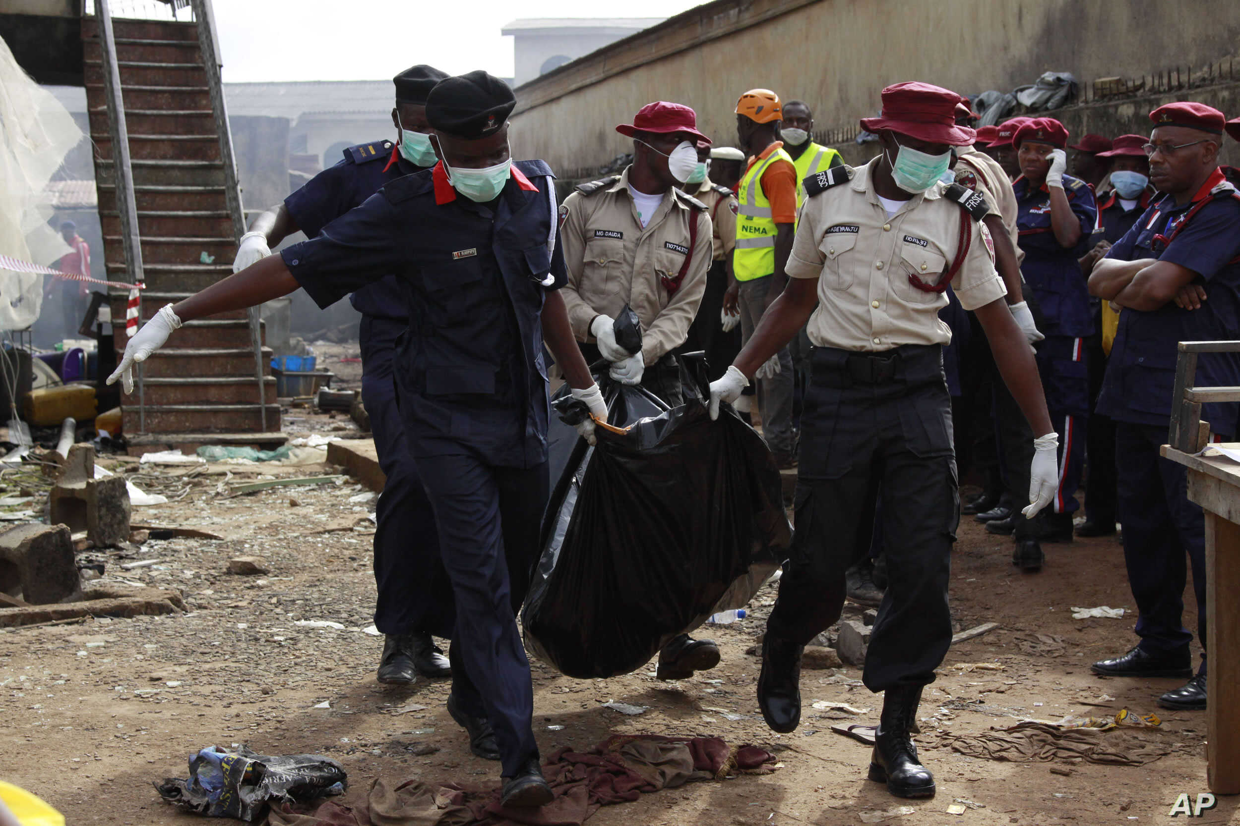 Rescue workers carry bodies at the site of a plane crash in Lagos, Nigeria, June 4, 2012.