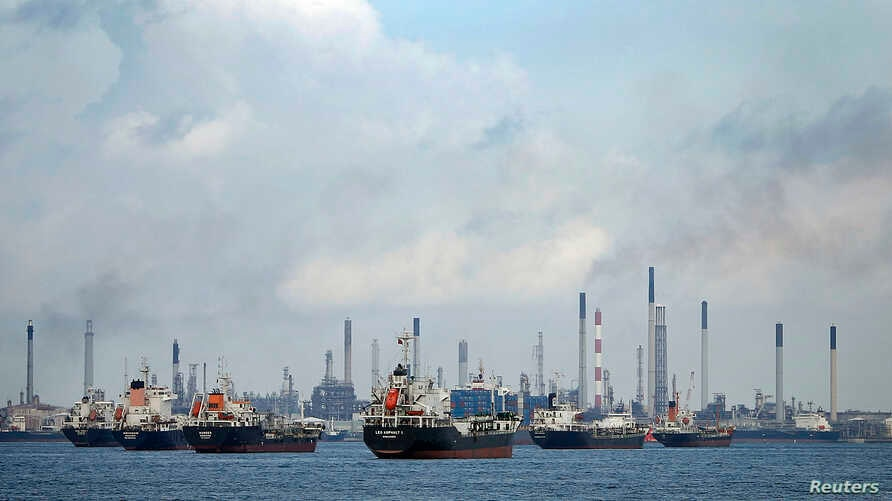 FILE - Ships are seen anchored in front of a refinery on Singapore's Bukom Island, July 6, 2014.