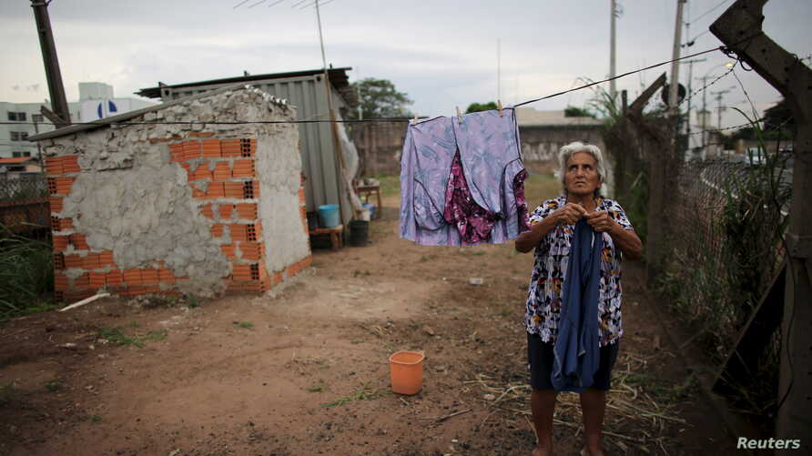 FILE - Claudia Rodrigues, 71, hangs up laundry in front of her home, which is a shipping container, next to a road in Campinas, Sao Paulo state, Brazil, March 22, 2016. Informal settlements set up by those who say they have nowhere else to live are n
