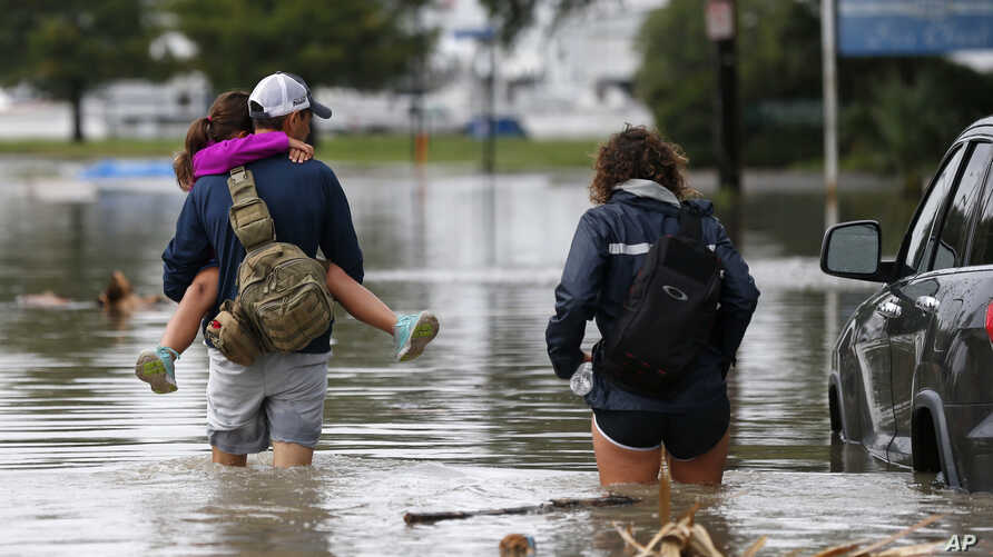 Don Noel carries his daughter Alexis, 8, with his wife Lauren, right as they walk through a flooded roadway to check on their boat in the West End section of New Orleans, June 21, 2017.