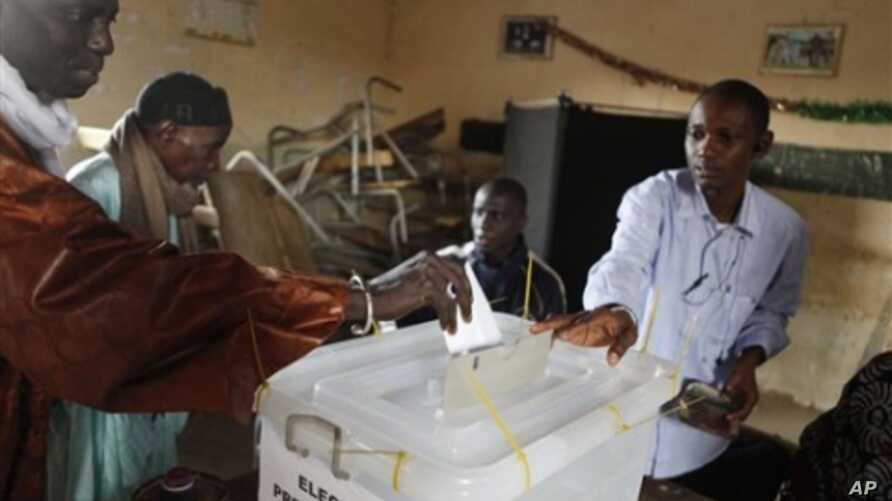 A poll worker helps a voter cast his ballot for president at a polling station in the Cambarene neighborhood of Dakar, Senegal, Sunday, Feb. 26, 2012