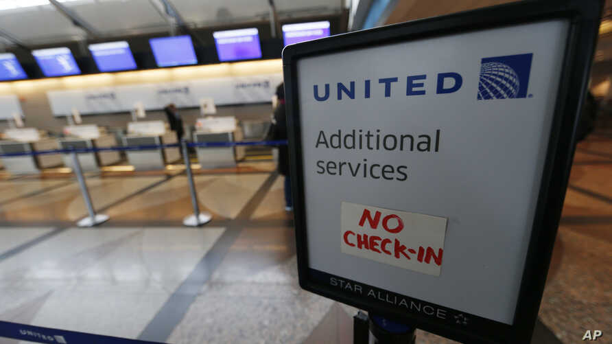 FILE - A piece of tape is affixed to a sign marking an empty line at the United Airlines ticket counter at Denver International Airport, April 16, 2016, in Denver, Colorado.