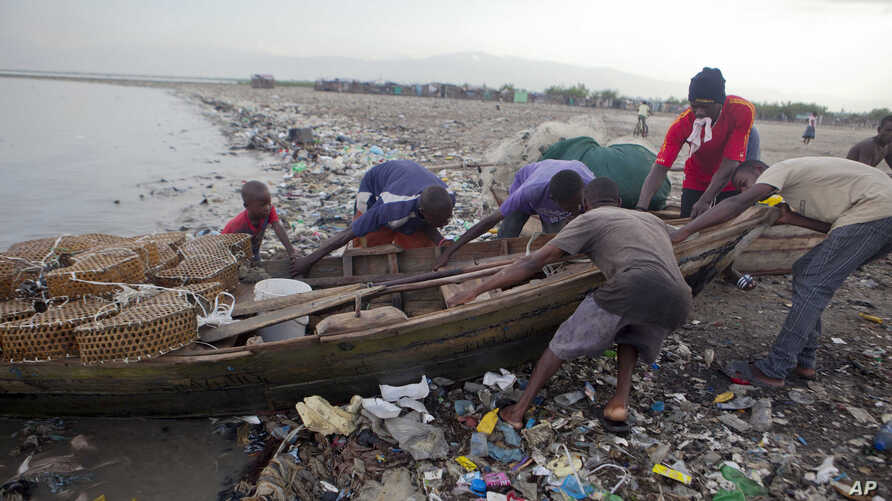 Fishermen remove their wooden boat from the sea as a precaution against Hurricane Irma, in the seaside slum of Port-au-Prince, Haiti, Sept. 6, 2017. The northern parts of the Dominican Republic and Haiti could see 10 inches of rain.