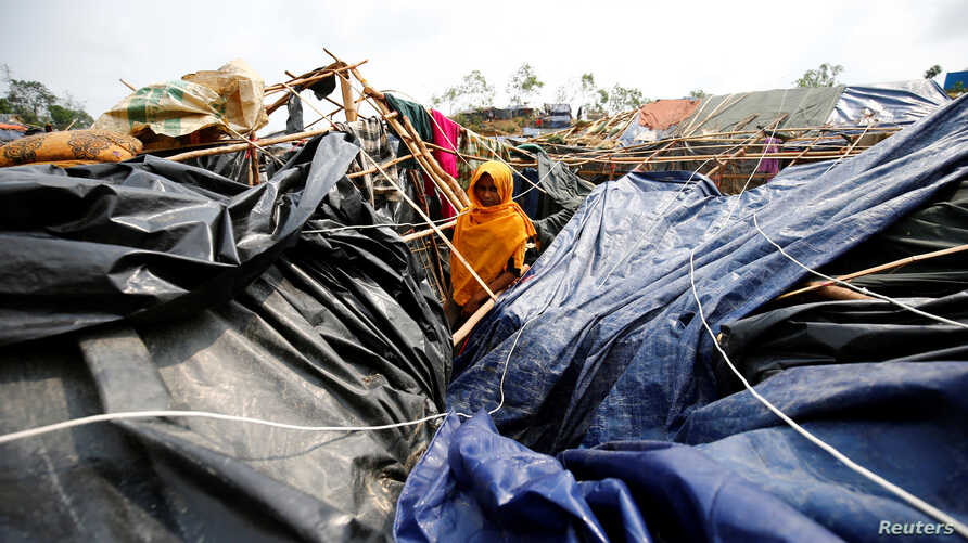 A young Rohingya refugee stands in her house which has been destroyed by Cyclone Mora at Balukhali  Refugee Camp in Cox's Bazar, Bangladesh, May 31, 2017.