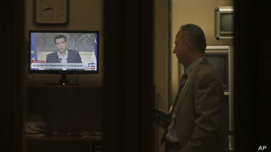 Greek Prime Minister Alexis Tsipras is seen on a screen during a televised address to the nation, as a staffer of the Greek Presidential Palace looks on, in Athens, Aug. 20, 2015.