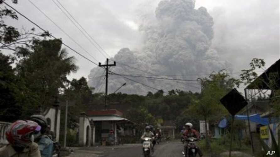 Motorists ride as pyroclastic material from the eruption of Mount Merapi billows in the background in Cangkringan, Yogyakarta, Indonesia, 31 Oct 2010