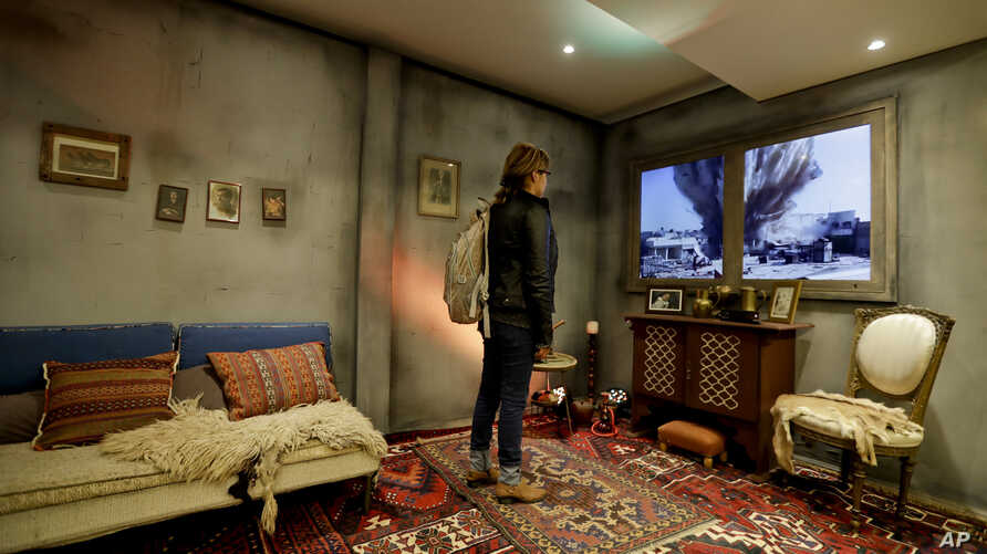 A woman watches video inside a mock Syrian home, set up by Amnesty International at a subway station in Buenos Aires, Argentina, Sept. 19, 2016. Argentina's President Mauricio Macri pledged his country would accept 3,000 Syrian refugees.