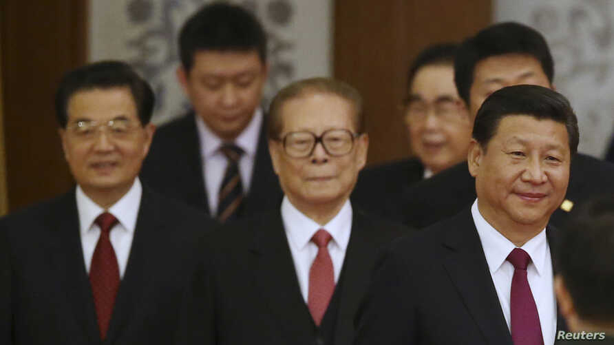 China's President Xi Jinping (R) walks with retired leaders Jiang Zemin (C) and Hu Jintao (L) as they arrive at the National Day Reception to mark the 65th anniversary of the founding of People's Republic of China, at the Great Hall of the People, in