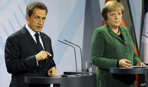 German chancellor Angela Merkel, right, and French President Nicolas Sarkozy talk to the media after a meeting on the financial crisis in Berlin, Germany, Sunday, Oct. 9, 2011.
