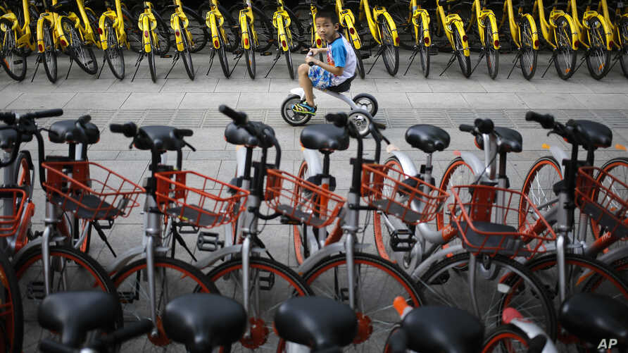 FILE - A child rides past bicycles from bike-sharing companies parked along a sidewalk in Beijing, Aug. 31, 2017. A report says China's factory activity expanded in September at the fastest pace in five years, indicating a healthy outlook for the wor
