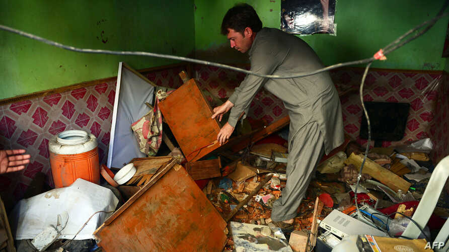 A Pakistani resident inspects a damaged television at a network office following an overnight bomb blast in Karachi, March 15, 2013.