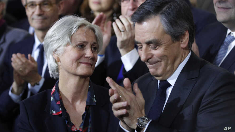 Conservative presidential candidate Francois Fillon applauds while his wife, Penelope, looks on as they attend a campaign meeting in Paris, Jan. 29, 2017. Financial prosecutors are investigating whether the former prime minister's wife was paid for w...