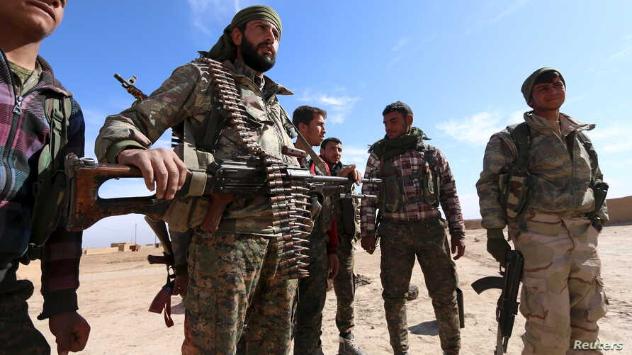 Syria Democratic Forces fighters carry their weapons in a village on the outskirts of al-Shadadi town, Hasaka countryside, Syria, Feb. 19, 2016.