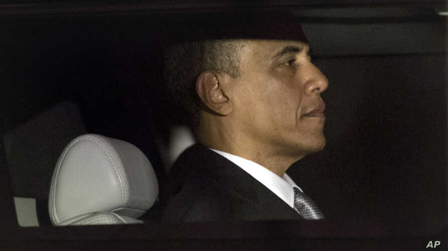 President Barack Obama is seen through the window of a limo as he returns to the White House for the first time since his victory on election day, in Washington, Nov. 7, 2012.