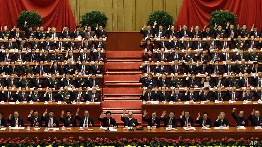 China's leaders raise their hands to show approval for a work report at the closing ceremony for the 18th Communist Party Congress, Beijing, November 14, 2012.