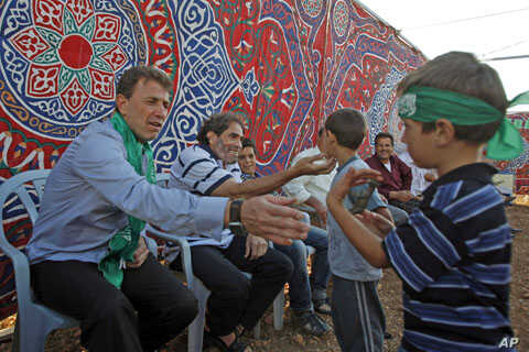 Freed Palestinian prisoner Nael Barghouti (L), who served 33 years in an Israeli jail, more time than any other Palestinian released in a trade for Israeli soldier Gilad Shalit, greets a child along with Fakhri Barghouti (C), who also was released, a