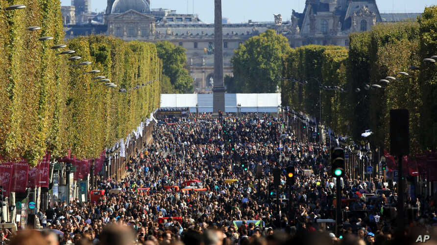 """People walk on the Champs Elysees during the """"day without cars"""", in Paris, France, Sept. 27, 2015."""